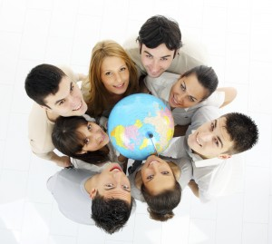 Group of a young students holding globe and looking at camera. View from above.